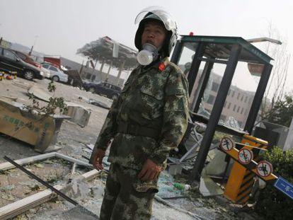 Um policial vigia área da explosão.