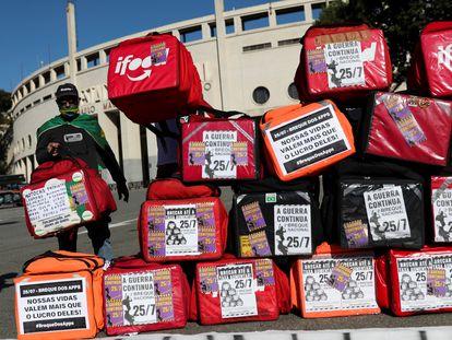 Motoboy ao lado de mochilas de entregas em frente ao estádio do Pacaembu, em São Paulo. durante segundo breque dos apps.