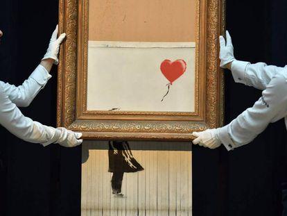 Empregados da Sotheby's carregam a obra semidestruída de Banksy.