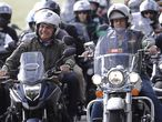 Brazil's President Jair Bolsoanro, left, takes a motorcycle tour with supporters representing the moto clubs in honor of Mother's Day, in Brasilia, Brazil, Sunday, May 9, 2021. (AP Photo/Eraldo Peres)