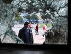 A man looks through a broken window of a vandalized police station following a protest against poverty and police violence in Bogota, Colombia, May 5, 2021. REUTERS/Luisa Gonzalez
