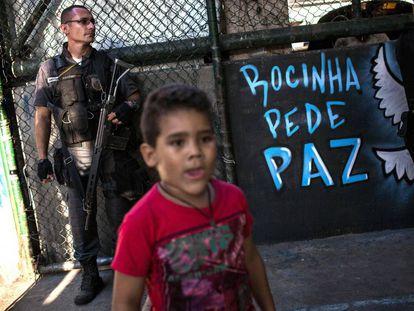 Uma criança e um policial na quadra onde moradores da Rocinha pediram à volta da sua rotina.