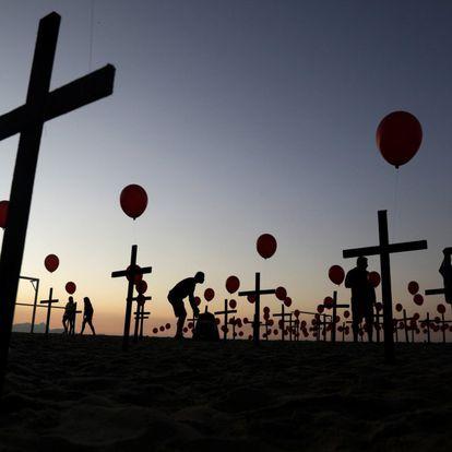 Instalación de la ONG Río de Paz en la playa Copacabana (Río de Janeiro) en memoria de los fallecidos en Brasil por coronavirus. El país, el más afectado en el subcontinente, está a punto de superar el umbral de los 100.000 muertos, tras haber llegado a 99.572 fallecidos el sábado.