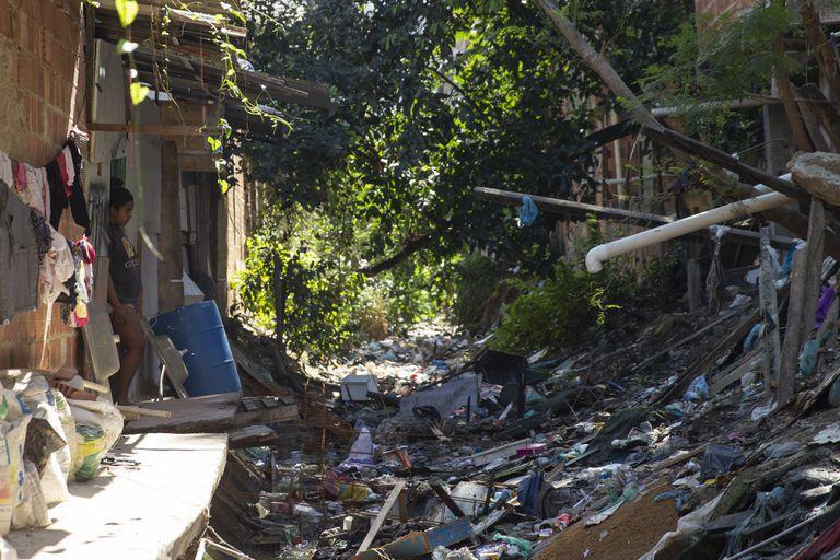 Área no Complexo do Alemão, com lixo e esgoto a céu aberto.
