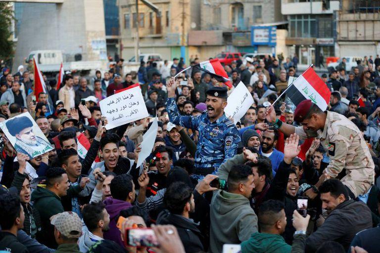Manifestantes carregam policiais iraquianos comemorando a vitória sobre o EI em Bagdá.