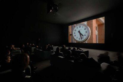 Pessoas assistindo ao filme 'The Clock' de Christian Marclay.