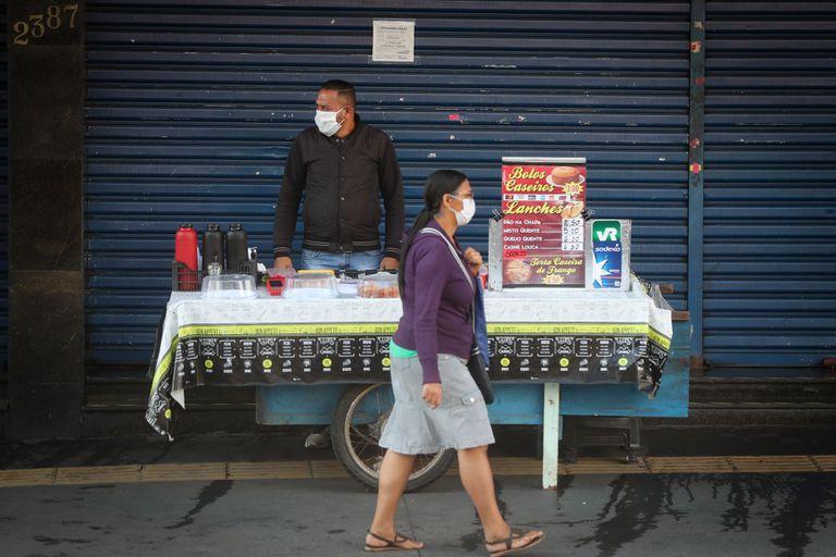 Uma mulher passa por um vendedor ambulante no centro de São Paulo, ambos usando máscara de proteção, nesta segunda-feira.