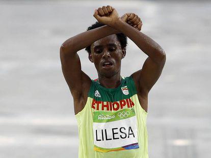Feyisa Lilesa faz seu gesto de protesto ao cruzar a linha de chegada.