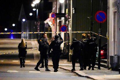 Vários policiais cruzam a área isolada para investigar o ataque, nesta quarta-feira, na cidade norueguesa de Kongsberg.