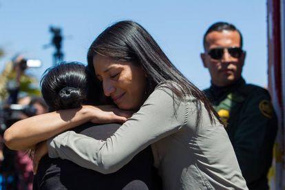 Jeanette Lorenzo abraça sua mãe na fronteira, vista pelo lado mexicano.