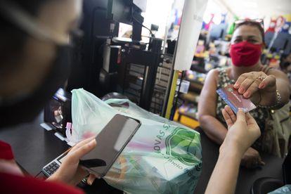 Uma mulher faz compras utilizando seu cartão Mumbuca, em Maricá.