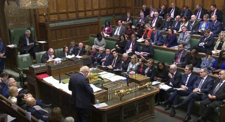 Boris Johnson, de costas, fala nesta terça-feira no Parlamento britânico.