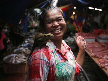 Uma mulher leva em seu ombro um rato num mercado de Maeklong, na periferia de Bangkok (Tailândia) em 20 de setembro.