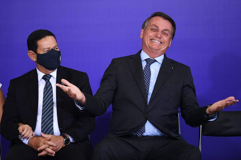 Bolsonaro é observado pelo vice, Hamilton Mourão, durante cerimônia no Palácio do Planalto, na segunda.