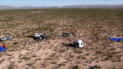 A cápsula que transportou o ator William Shatner de 'Star Trek' e três outros passageiros em um voo suborbital rodeada por pessoal de terra após aterrissar de paraquedas perto de Van Horn, Texas, EUA.