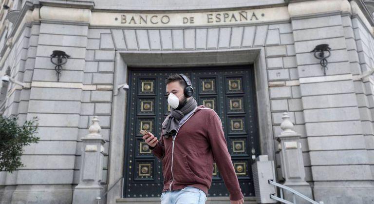 Pedestre caminha em frente ao Banco da Espanha, após o relaxamento das medidas de isolamento em Barcelona.