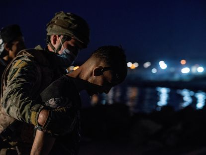 Soldado conduz imigrante que saía da água na praia de El Tarajal, em Ceuta.