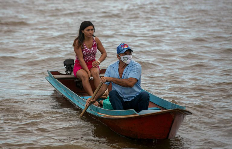 Moradores atravessam rio em Breves, no Pará, que vive surto de coronavírus.