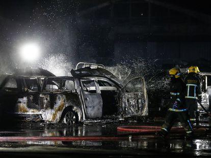 Três bombeiros apagam um incêndio provocado durante os protestos da noite de 14 de julho em Santiago.
