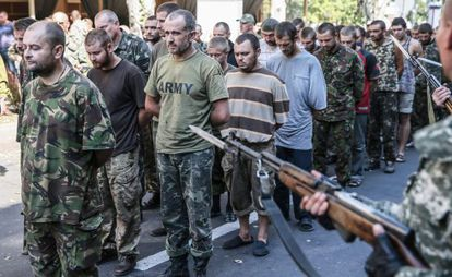 Pró-russos escoltam prisioneiros de guerra em Donetsk.