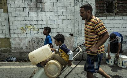 Pai e filhos carregam galões de água em Caracas