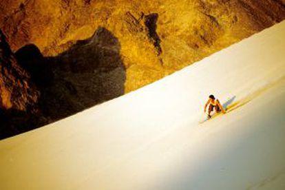 Descida de sandboard no deserto peruano.