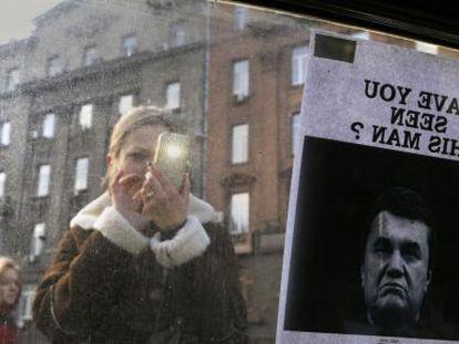"""Ucraniana tira foto de letreiro de """"Procura-se"""" de Yanukóvich."""