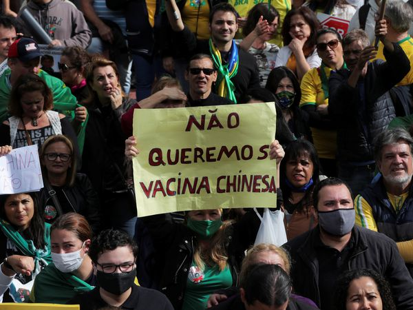 """A woman holds a placard reading """"We don't want Chinese vaccine"""" as demonstrators protest against Sao Paulo state governor Joao Doria and China's Sinovac potential coronavirus disease (COVID-19) vaccine in Sao Paulo, Brazil, November 1, 2020. REUTERS/Amanda Perobelli"""