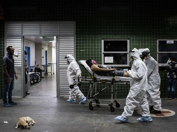 AME9884. MANAOS (BRASIL), 14/05/2020.- Trabajadores del Servicio de Atención Médica de Urgencia de Brasil (SAMU) trasladan a una paciente con covd-19 al hospital este jueves, en Manaos, estado de Amazonas (Brasil). El estado de Amazonas, el más extenso de Brasil, sufre en sus carnes el azote de la pandemia. De entre las 20 ciudades brasileñas más golpeadas en número de muertes a cada 100.000 habitantes, hay 13 situadas en Amazonas, según cálculos publicados esta semana. Con unos cuatro millones de habitantes -unos 185.000 de ellos indígenas-, la región suma más de 15.000 contagios y el 90 % de sus municipios ya están afectados por la pandemia. EFE/ Raphael Alves