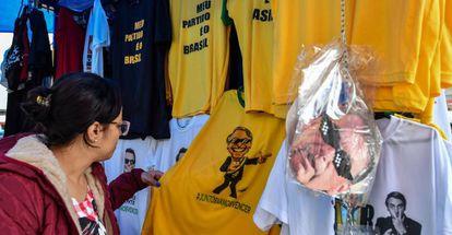 Mulher olha camiseta com a imagem do candidato Jair Bolsonaro em shopping popular no centro de São Paulo.
