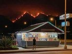 FILED - 10 September 2020, US, Monrovia: A man stands in front of a takeaway restaurant as flames burn through the hills of the Angeles National Forest in the background amid wildfires in California. Photo: David Swanson/ZUMA Wire/dpa 10/09/2020 ONLY FOR USE IN SPAIN