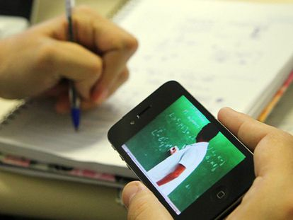 Estudante assiste a uma aula em vídeo pelo celular.