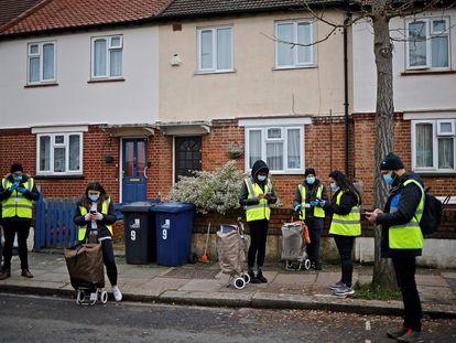 Voluntários se preparam para distribuir exames caseiros de covid-19, em Londres, nesta quarta.