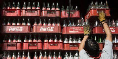 Um trabalhador empilha caixas de garrafas de Coca-Cola, no México.