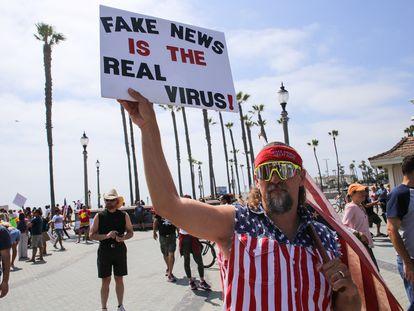 """Manifestante na Califórnia levanta cartaz que diz """"Fake news são os vírus de verdade"""", em maio."""