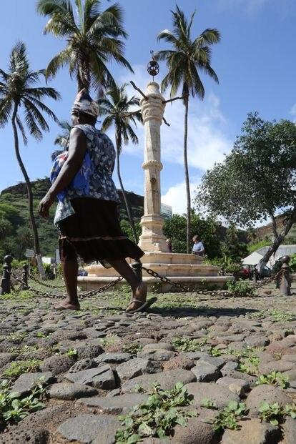 Mulher caminha em frente ao pelourinho da Cidade Velha (Cabo Verde), um lugar onde os negros escravizados eram castigados.