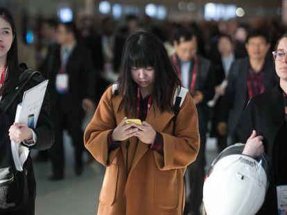Mulher lê algo no celular.