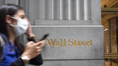 Mulher com máscara passa em frente a um edifício de Wall Street, o centro financeiro de Nova York.