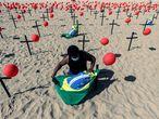 -FOTODELDIA- GRAF049. RÍO DE JANEIRO (BRASIL), 08/08/2020.- Un activista instala una bandera de Brasil en una representación escénica de la ONG Río de Paz por las víctimas del COVID-19 hoy, en la playa de Copacabana en Río de Janeiro (Brasil). Con mil globos rojos en las arenas de la playa y cien de ellos fijados en cien cruces negras se rindió homenaje a los 100 mil brasileños fallecidos por la pandemia de coronavirus y se manifestaron en contra de la forma en que el Gobierno ha gestionado la crisis sanitaria. EFE/Antonio Lacerda