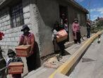 "Residents wearing protective face masks hold food boxes distributed by the government during a lockdown to contain the spread of COVID-19, on the outskirts of Quito, Ecuador, Wednesday, May 27, 2020. Across the region, nearly 30 million more people are expected to find themselves in ""situations of poverty"" and another 16 million among the extreme poor, the U.N. estimates. (AP Photo/Dolores Ochoa)"