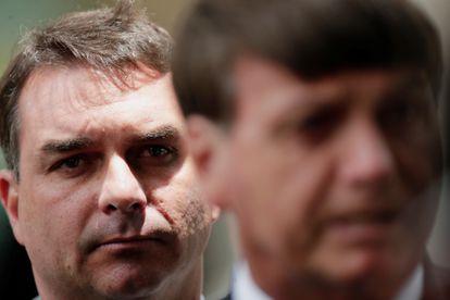 O senador Flávio Bolsonaro observa seu pai, o presidente Jair Bolsonaro, em 27 de janeiro.