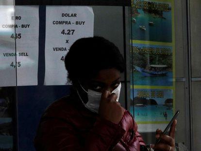 Uma mulher usando uma máscara de proteção sai de uma casa de câmbio no Rio de Janeiro, em fevereiro de 2020.