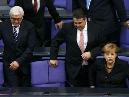 Angela Merkel no Bundestag com os titulares de Exteriores, Frank-Walter Steinmeier (esquerda), e Economia, Sigmar Gabriel.