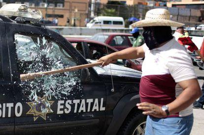 Homem quebra o vidro de um carro policial em Chilpancingo.