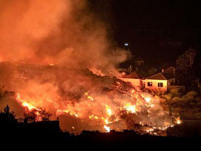 A lava do vulcão Cumbre Vieja avança sobre as casas da ilha espanhola de La Palma, nas Canárias, na noite de domingo.
