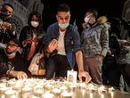 People lights candle outside the Notre-Dame de l'Assomption Basilica in Nice on October 29, 2020 in tribute to the three victims of a knife attacker, cutting the throat of at least one woman, inside the church of the French Riviera city. (Photo by Valery HACHE / AFP)