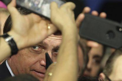 O presidente Jair Bolsonaro tira fotos com seus apoiadores em Brasília, no dia 21 de maio.