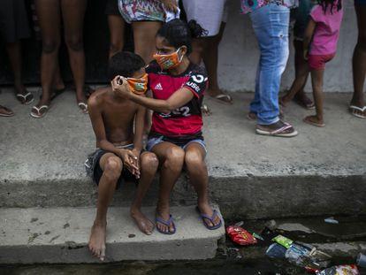Uma menina ajuda um menino a colocar uma máscara doada enquanto os moradores fazem fila para receber sacolas de comida grátis, no Rio de Janeiro.