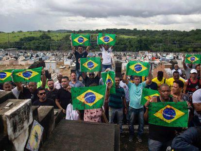 Manifestantes levam bandeiras do Brasil sujas de tinta vermelha em protesto no cemitério Ricardo de Albuquerque. no Rio, no último dia 10, contra a ação do Exército que causou duas mortes.