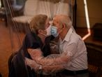Agustina Cañamero, 81, and Pascual Pérez, 84, hug and kiss through a plastic film screen to avoid contracting the new coronavirus at a nursing home in Barcelona, Spain, Monday, June 22, 2020. The Ballesol Fabra i Puig elderly care center installed the screens to resume relatives' visits to residents 102 days after a strict, nationwide lockdown separated them. As she and her husband broke out into tears while kissing through layers of protective masks and the transparent plastic film, Cañamero said that the couple had never spent such long time with no physical contact in 59 years of marriage. Nursing homes in Spain have been particularly hit by the novel virus, which has claimed at least 28,300 lives nationwide. (AP Photo/Emilio Morenatti)